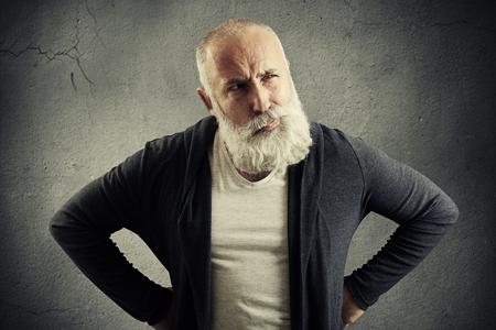 desconfianza: hombre mayor que mira con recelo a algo sobre la pared gris oscuro Foto de archivo