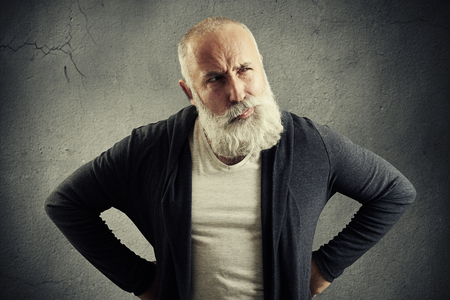 suspiciously: senior man looking with distrust at something over dark grey wall Stock Photo