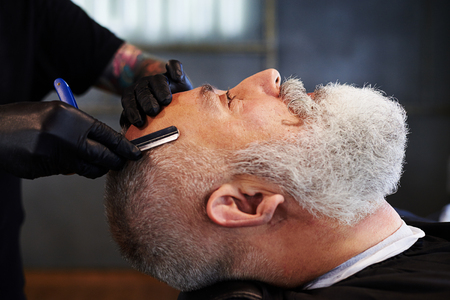 gray haired: portrait of senior bearded man in barbershop. barber shaving man with straight razor