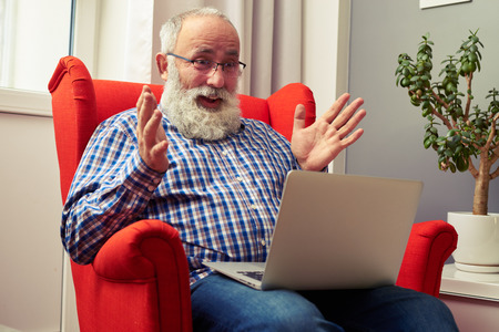 grey haired: amazed senior man sitting on the chair and looking at laptop