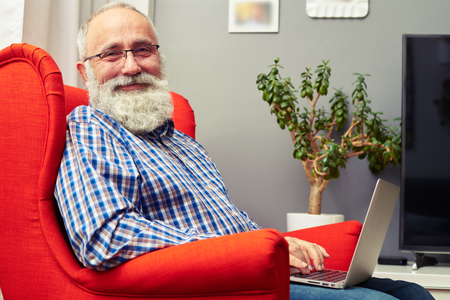 aged: smiley senior man working with laptop and looking at camera