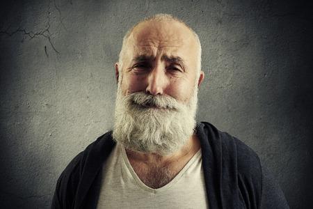 sorrowful: sorrowful senior man with grey-haired beard over dark background Stock Photo