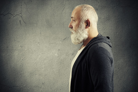 old man beard: portrait of handsome senior man with grey-haired beard with empty copyspace over grey background