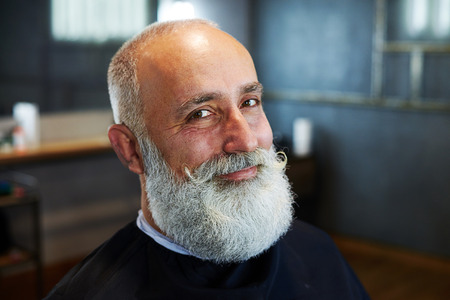 white beard: portrait of smiley stylish man with grey-haired beard and mustache in barbershop