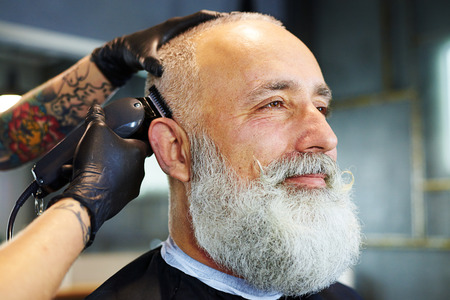 barbershop: sideview portrait of handsome bearded man in professional barbershop. barber shaving beard with electric razor Stock Photo