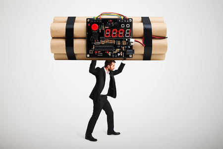 human time bomb: small businessman carrying big bomb over light grey background