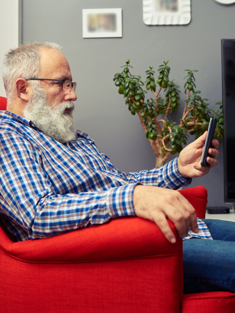 white beard: bearded senior man in checkered shirt sitting on the chair and looking at his smartphone at home