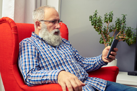 using phone: senior man resting on the chair and looking at hid smartphone at home Stock Photo