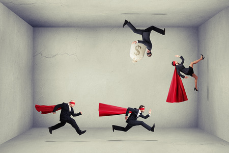 supergirl: superheroes trying to catch criminals in empty grey room Stock Photo