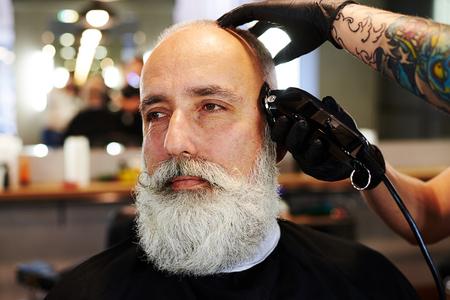 electric razor: portrait of bearded senior man in barbershop. barber working with electric razor