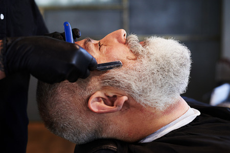 straight razor: portrait of senior man in barbershop. barber shaving man with straight razor Stock Photo