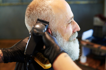 sideview: sideview portrait of senior bearded man in professional barbershop. barber shaving beard with electric razor