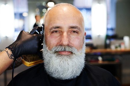 gray haired: portrait of bearded handsome senior man in barbershop. barber working with electric razor