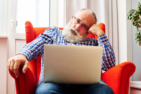 fatigued: fatigued senior man sitting on the red chair and looking at laptop Stock Photo