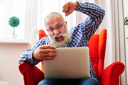 brandishing: emotional senior man brandishing his fist and screaming at laptop at home Stock Photo