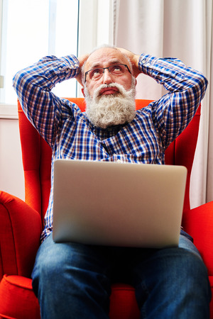 fatigued: fatigued senior man sitting on the chair with laptop and looking up
