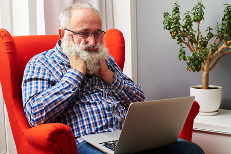 tedious: bearded senior man looking at laptop and boring at home Stock Photo