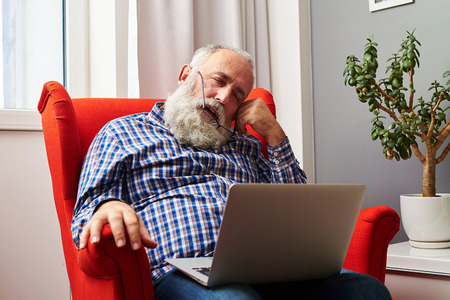 fatigued: bearded senior man sleeping with laptop on the red chair at home