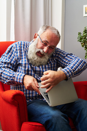 grey haired: screaming angry man sitting on the red chair and breaking his laptop Stock Photo