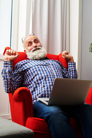 grey haired: tired senior man with laptop on the chair at home