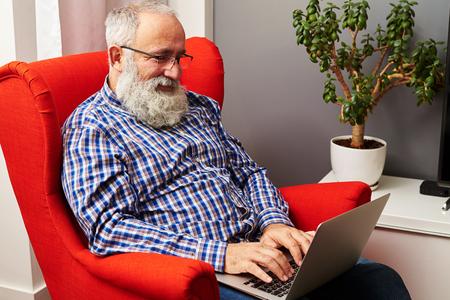 hombres trabajando: Hombre mayor sonriente que trabaja con el ordenador port�til en casa Foto de archivo
