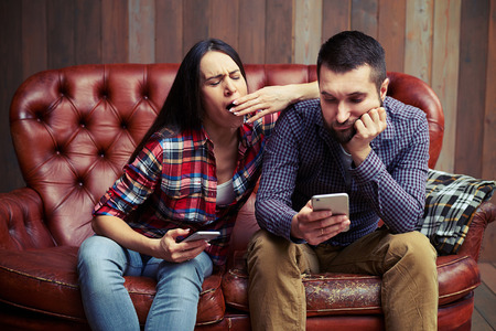 tiresome: boring couple sitting on sofa and looking at smartphone