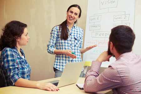 casual woman: young speaker standing near white board and explaining something to her colleagues in office