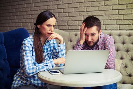 despondent: portrait of despondent couple looking at laptop