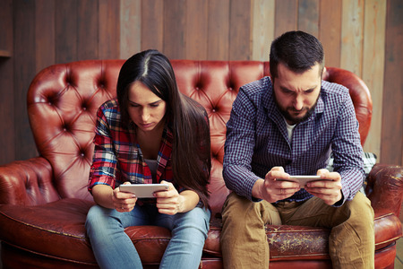 woman on cell phone: concept photo of smartphone addiction. young woman and man sitting on the sofa with smartphone and do not looking at each other