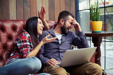 surfing the internet: young couple discussing something and laughing Stock Photo