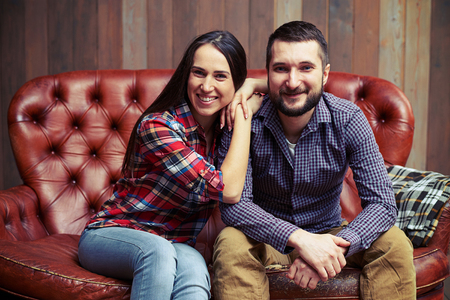 family portrait: portrait of young couple sitting on sofa and looking at camera