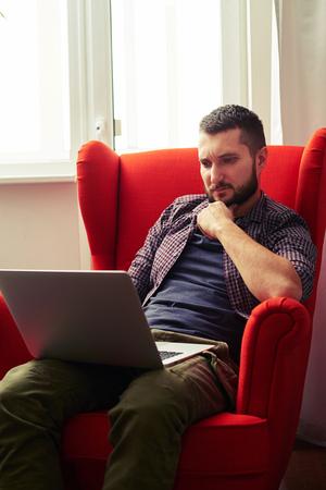 trabajando en casa: hombre joven pensativo sentado en la silla roja y el trabajo con ordenador portátil en casa