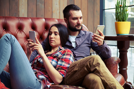 couple on couch: man and woman relaxing on the couch and using smartphones at home
