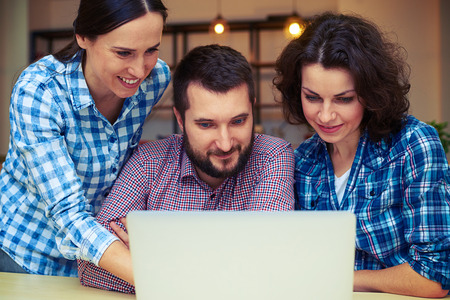 mates: cheerful team mates working with laptop in office Stock Photo