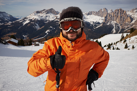 fassa: smiley skier showing thumbs up and looking at camera against mountainside Stock Photo