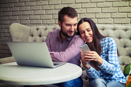 couple couch: smiley young couple sitting on sofa and using gadgets Stock Photo