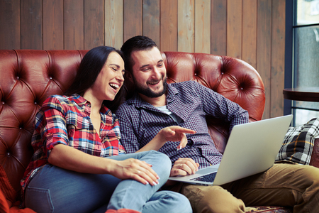 people relaxing: young couple looking at laptop and laughing