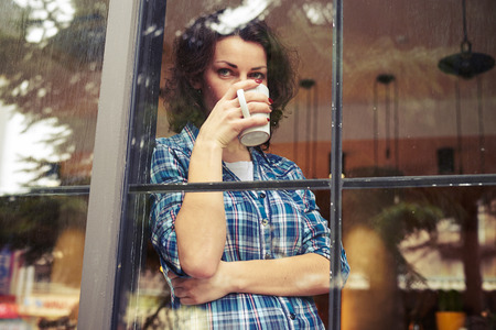 beautiful young woman standing near window, drinking the coffee and looking into the distance Stock Photo