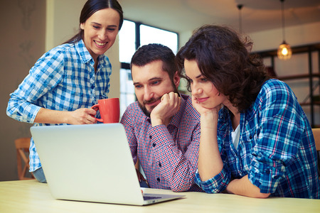 smiley friends watching interesting video on laptop Stock Photo