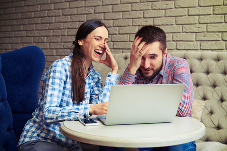 downcast: laughing woman and sad man sitting on sofa and looking at laptop