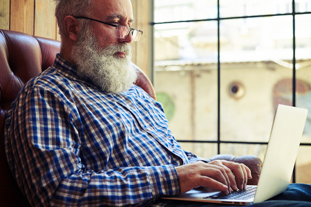 the thoughtful: bearded senior man in glasses sitting on the couch and working with laptop at home