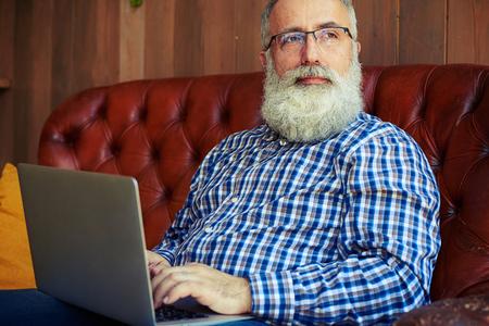 personen: nadenkende oude man zitten met een laptop en kijken naar raam Stockfoto