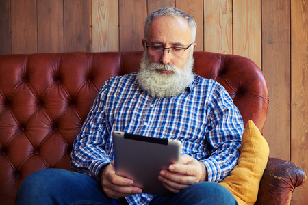 white beard: thoughtful middle-aged man with tablet pc resting on sofa at home