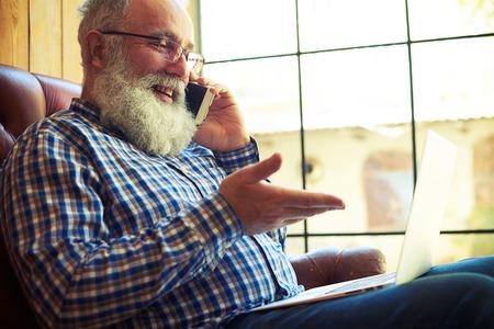 persona feliz: sonriente hombre mayor sentado en el sofá con ordenador portátil y hablando por el teléfono en el país