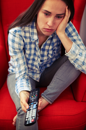 cheerless: sad woman holding remote control and watching tv at home