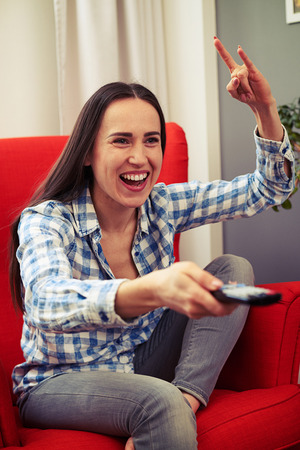 mujer viendo tv: emotional woman watching tv and showing rock sign Foto de archivo