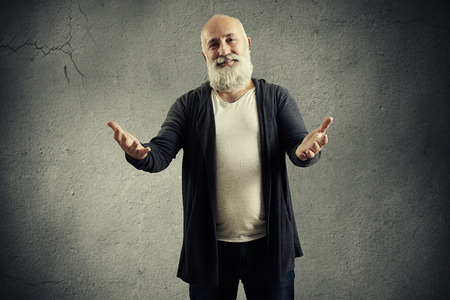 white beard: bearded man friendly pulling hand to the camera over dark background Stock Photo