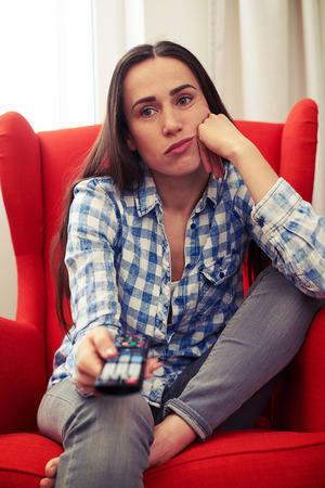 tiresome: young woman sitting on red chair and watching tiresome film Stock Photo