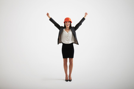 outwards: Happy smiling woman in formal wear and hard hat rising her hands upwards and outwards
