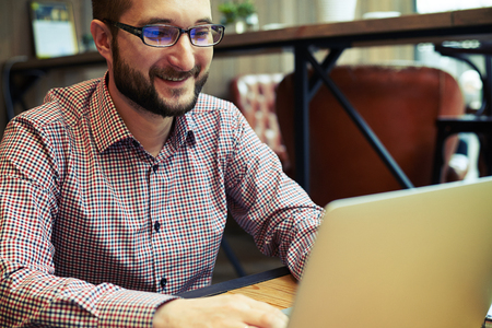 busy beard: Close up of smiling businessman with the glasses writing something with his laptop Stock Photo